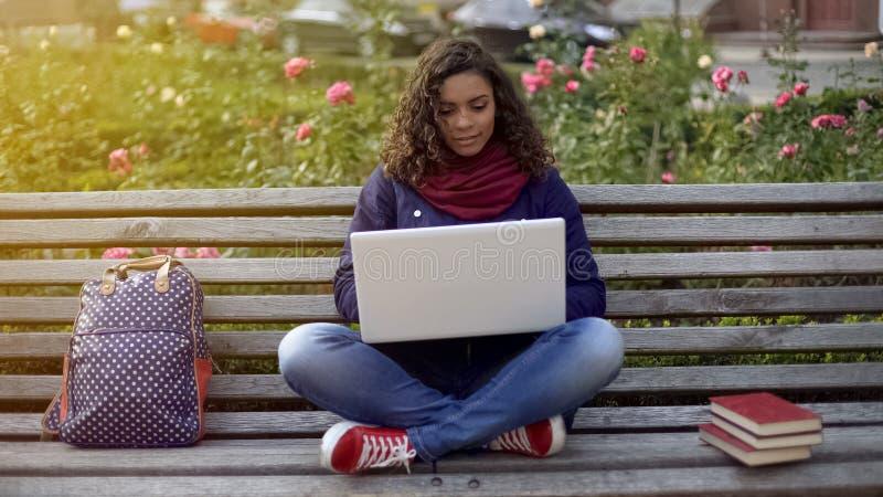 Giovane saggio di scrittura di signora della corsa mista sul computer portatile, studiante in pieno dell'ispirazione immagine stock libera da diritti