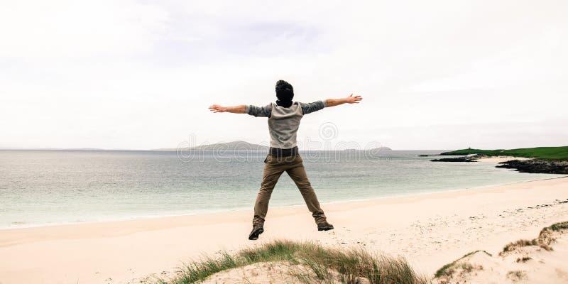Giovane salto di modello su una duna di sabbia con a braccia aperte B sabbiosa bianca fotografia stock libera da diritti