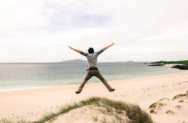 Giovane salto di modello su una duna di sabbia con a braccia aperte B sabbiosa bianca immagini stock libere da diritti