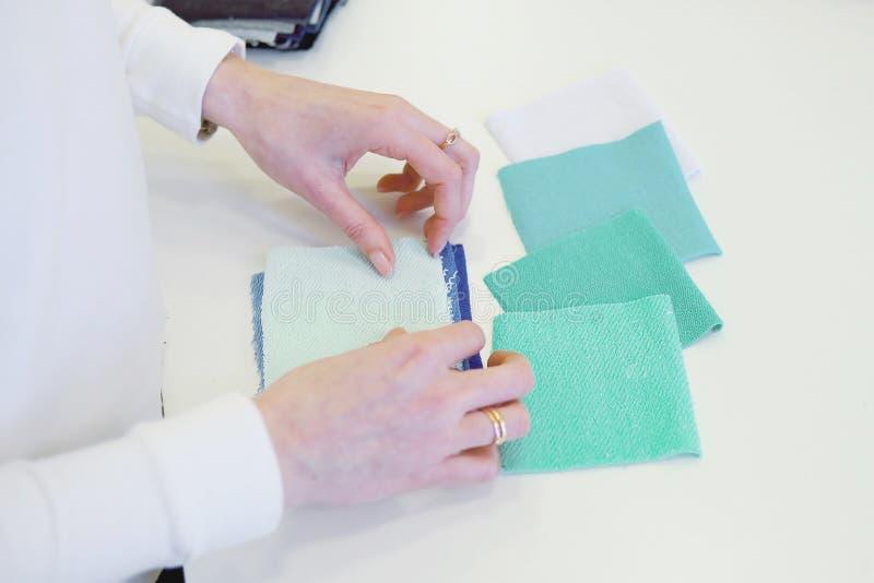 Giovane sarto da donna femminile che sceglie materiale dal catalogo in studio Adatti lo sguardo attraverso i tessuti mentre stann immagini stock