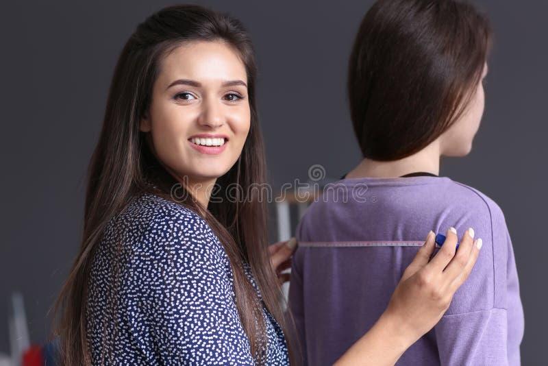 Giovane sarto femminile che prende le misure del cliente in atelier fotografia stock
