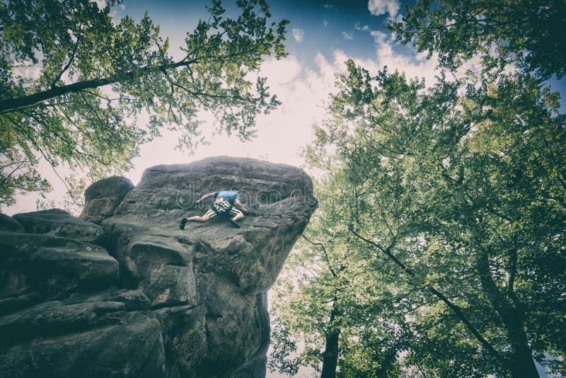 Giovane scalatore che appende da una scogliera fotografia stock