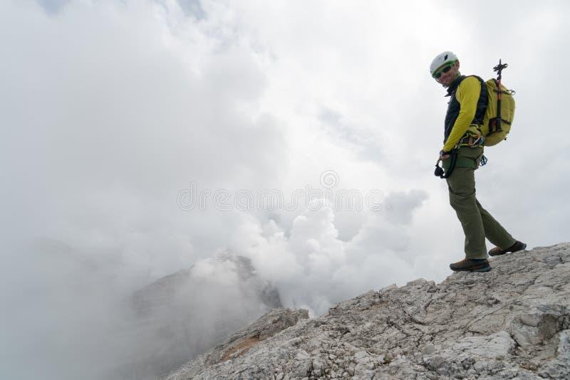 Giovane scalatore di montagna maschio su un picco di montagna della dolomia che gode della vista immagini stock
