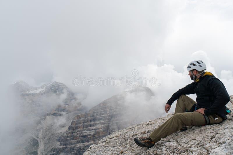 Giovane scalatore di montagna maschio su un picco di montagna della dolomia che gode della vista con la sua guida che sta dietro immagini stock