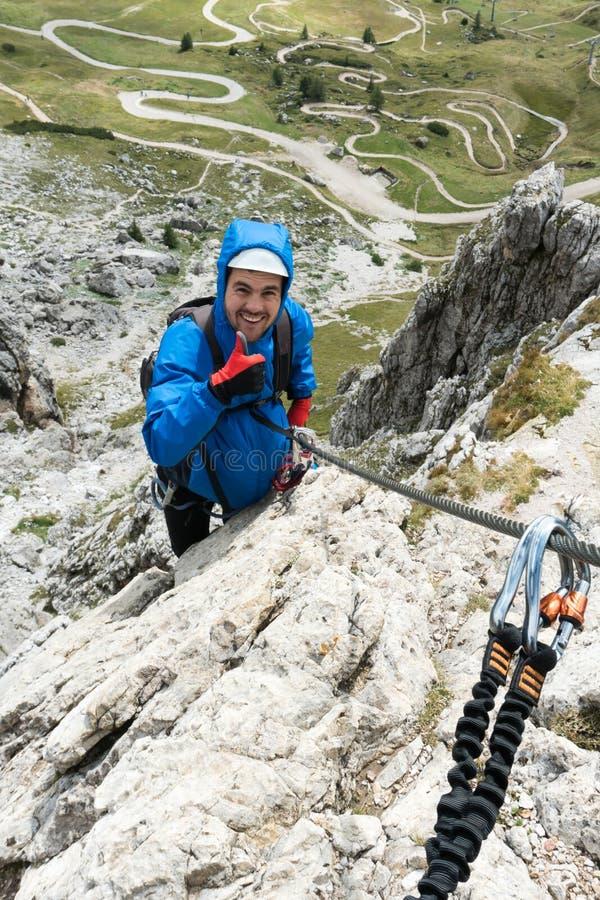 Giovane scalatore di montagna maschio sulla a via Ferrata nelle dolomia nel dare di Alta Badia pollici su immagine stock libera da diritti