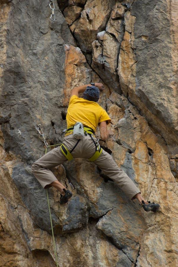 Giovane scalatore maschio che appende da una scogliera fotografie stock