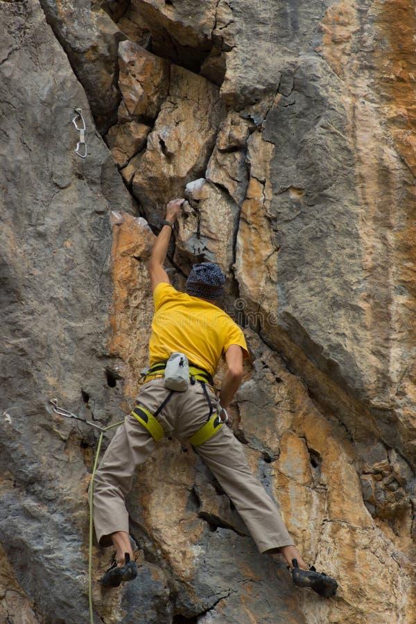 Giovane scalatore maschio che appende da una scogliera fotografie stock libere da diritti