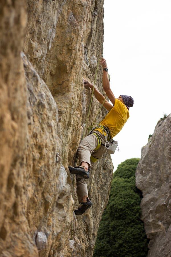 Giovane scalatore maschio che appende da una scogliera fotografia stock libera da diritti