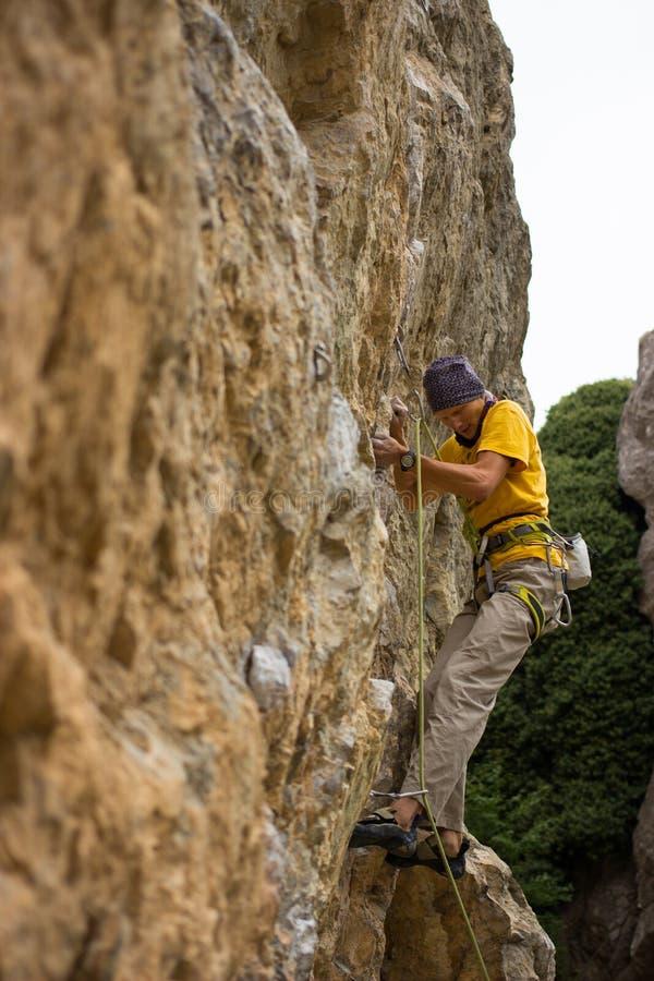 Giovane scalatore maschio che appende da una scogliera immagine stock libera da diritti