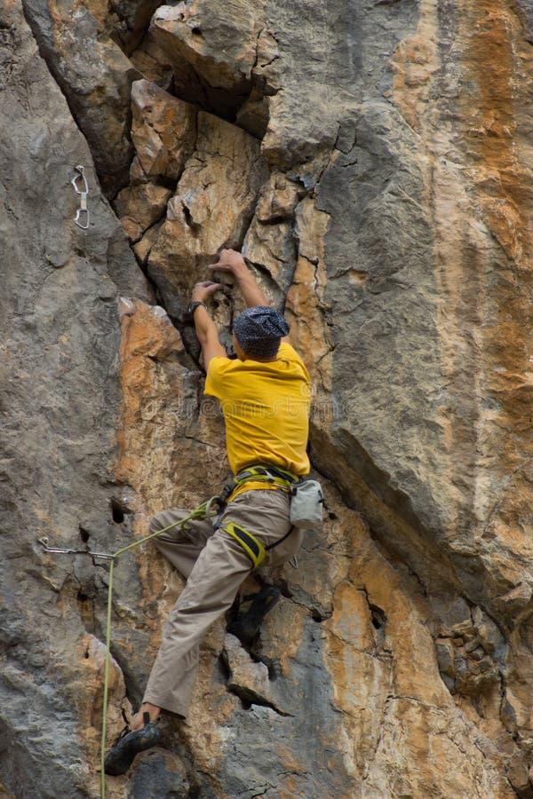 Giovane scalatore maschio che appende su una scogliera immagine stock