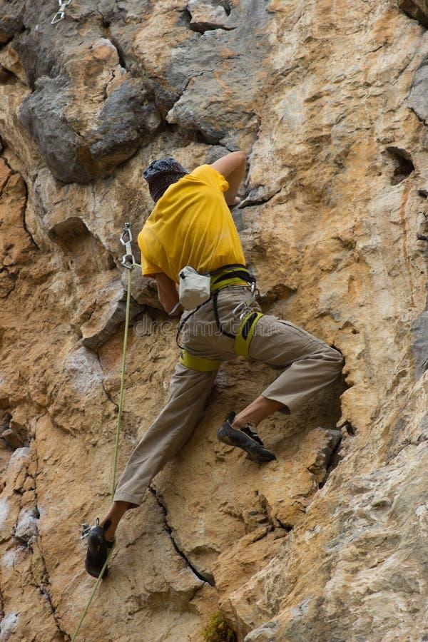 Giovane scalatore maschio che appende su una scogliera fotografia stock libera da diritti