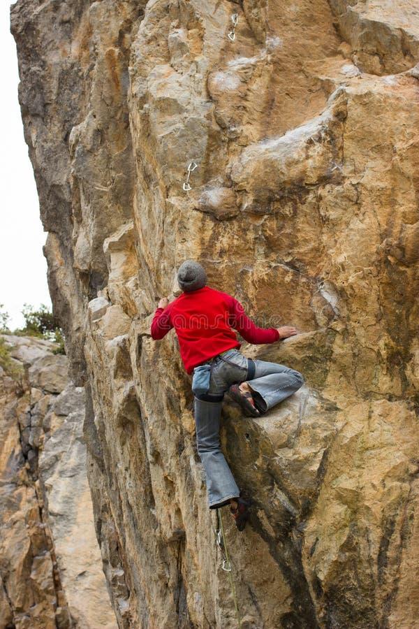 Giovane scalatore maschio che appende su una scogliera fotografie stock