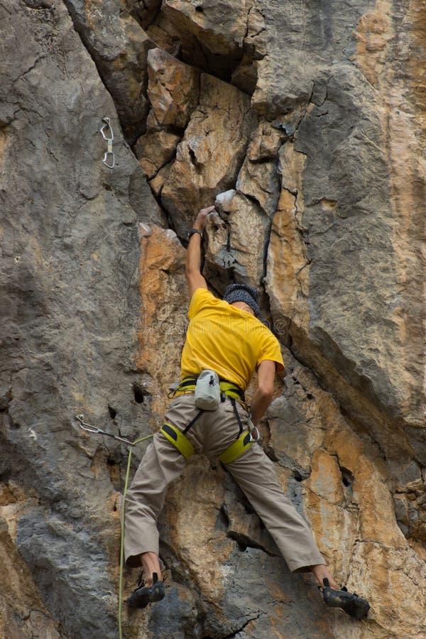 Giovane scalatore maschio che appende su una scogliera immagini stock