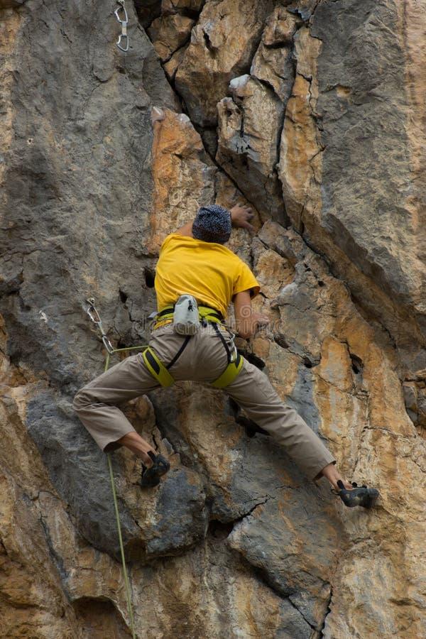 Giovane scalatore maschio che appende su una scogliera immagine stock libera da diritti