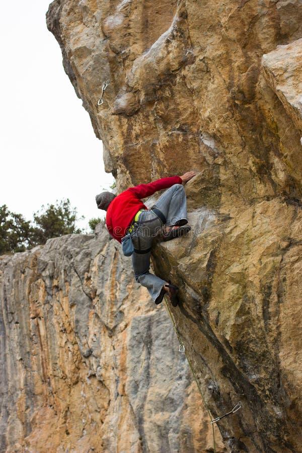 Giovane scalatore maschio che appende su una scogliera fotografia stock