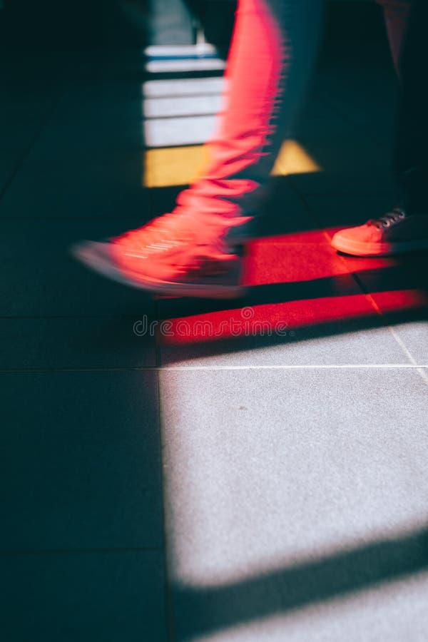 Giovane in scarpa da tennis che cammina sulla via Luce intensa che cade attraverso le finestre di vetro colorate sul pavimento fotografia stock libera da diritti