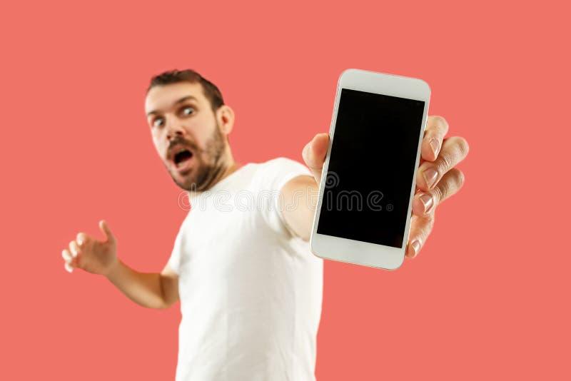 Giovane schermo bello dello smartphone di rappresentazione dell'uomo isolato su fondo di corallo nella scossa con un fronte di so fotografie stock libere da diritti