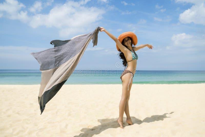 Giovane sciarpa sexy della tenuta della ragazza sulla spiaggia in bikini Concetto di rilassamento e di libert? immagine stock libera da diritti