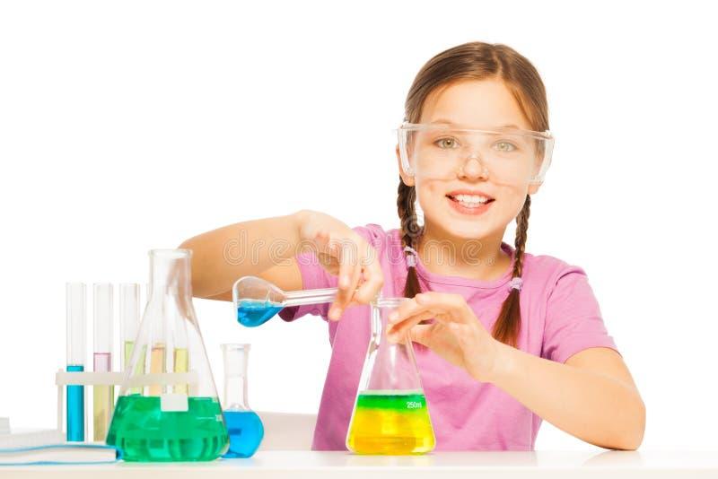 Giovane scolara che mescola i reattivi blu e gialli fotografie stock