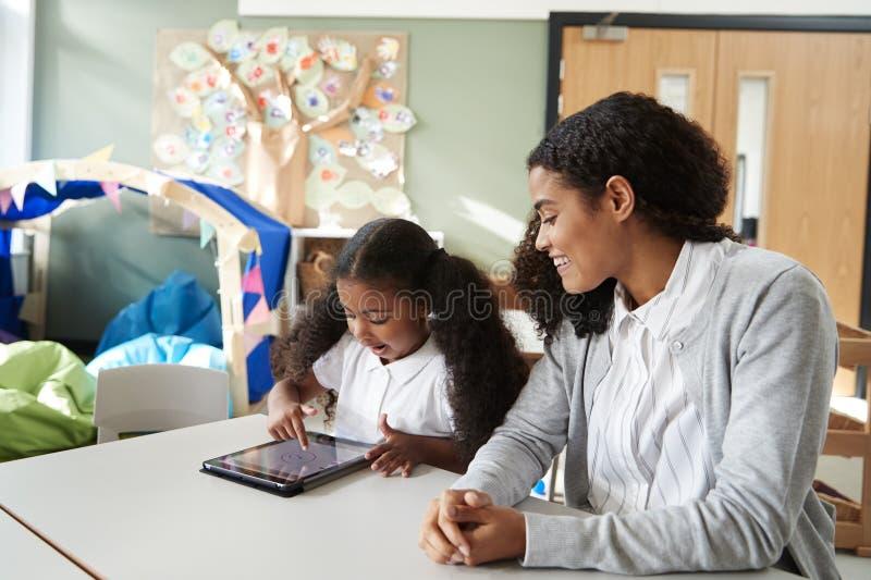 Giovane scolara nera che si siede ad una tavola in un'aula della scuola infantile facendo uso di un computer della compressa e ch immagini stock libere da diritti