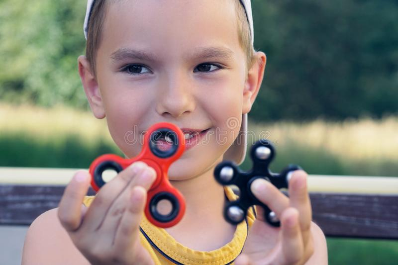 Giovane scolaro che tiene il giocattolo popolare del filatore di irrequietezza - ritratto alto vicino Bambino sorridente felice c immagini stock libere da diritti