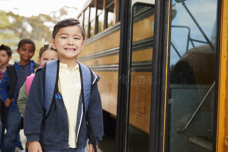 Giovane scolaro ed amici che aspettano per imbarcarsi sullo scuolabus fotografia stock libera da diritti