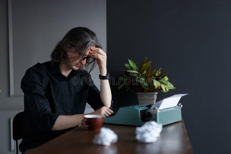 Giovane scrittore con una macchina da scrivere Giovane scrittore pensieroso davanti alla sua macchina da scrivere Tiro dello stud immagini stock libere da diritti