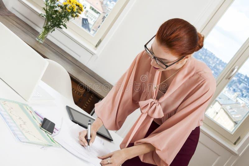 Giovane scrittura diritta della donna dell'ufficio su uno scrittorio immagine stock