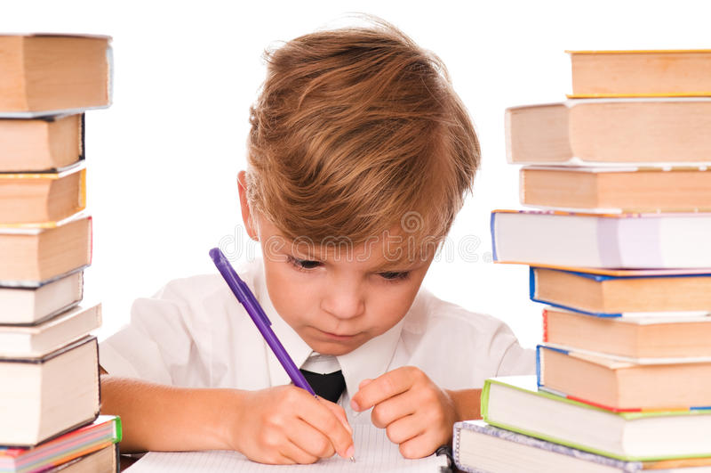 Giovane scrittura e libri del ragazzo immagini stock