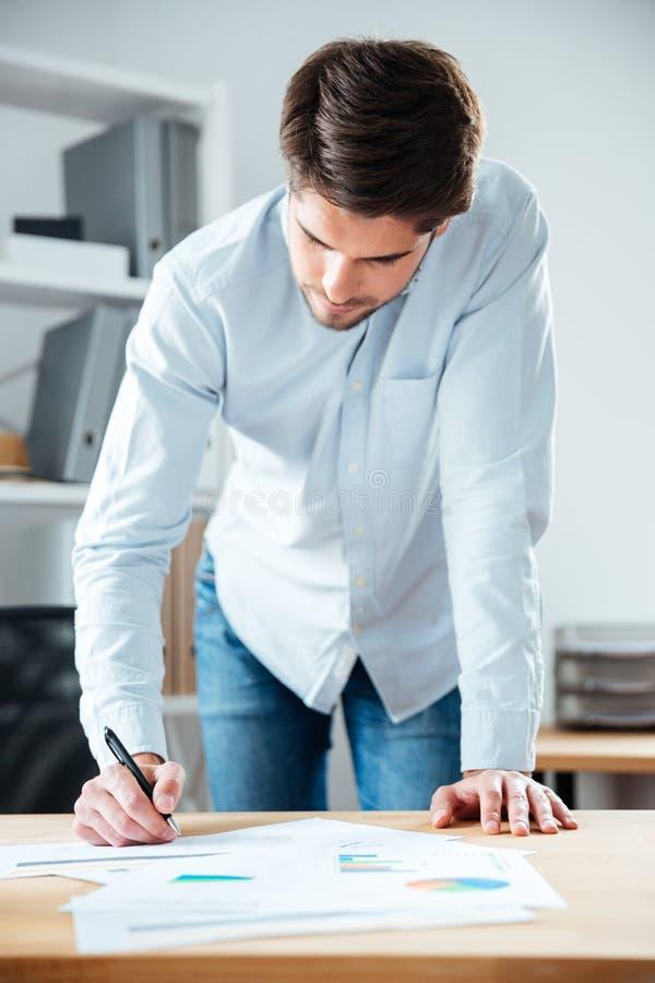 Giovane scrittura seria dell'uomo d'affari sulla tavola in ufficio immagini stock
