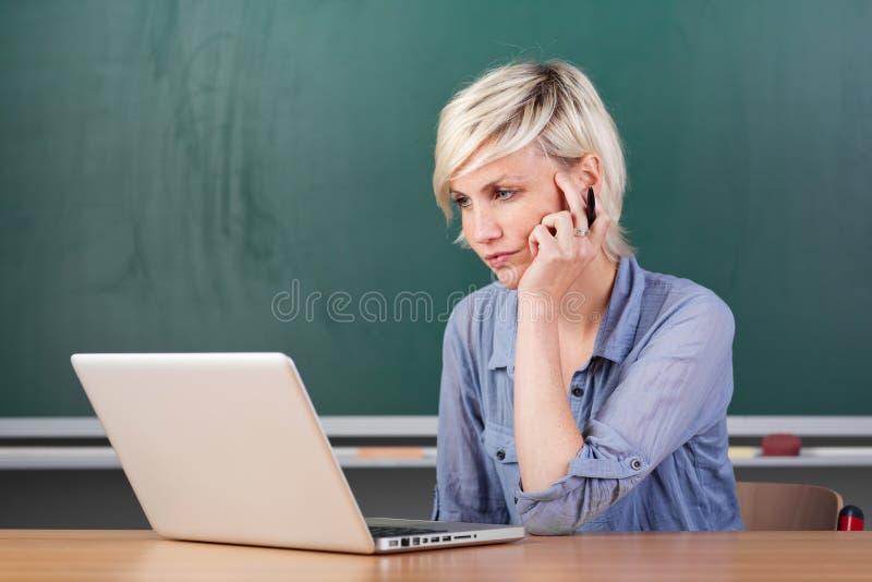 Giovane scuola seria di Using Laptop At dell'insegnante immagini stock