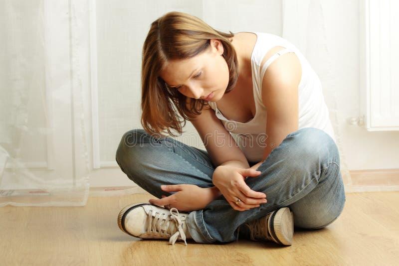 Giovane seduta femminile su Flor - depressione immagine stock libera da diritti