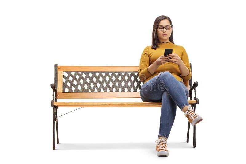 Giovane seduta femminile su un banco e scrivere su un telefono cellulare fotografia stock