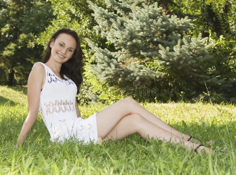 Giovane seduta femminile sul campo di erba al parco immagini stock