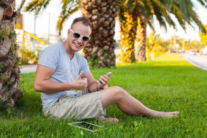 Giovane seduta turistica sotto la palma con il telefono cellulare e il tabl immagine stock libera da diritti