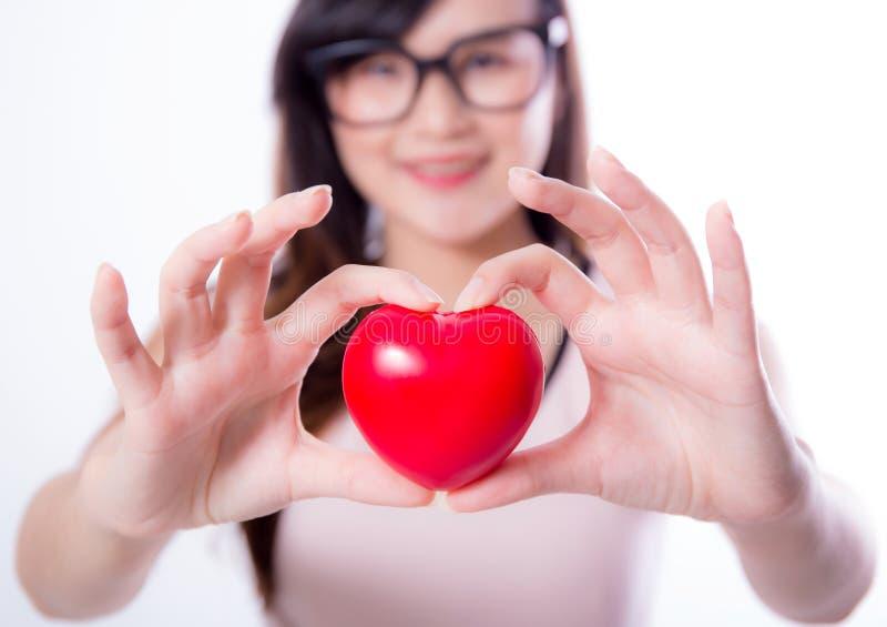 Giovane segno asiatico della mano del cuore di manifestazione della donna su fondo bianco immagine stock libera da diritti
