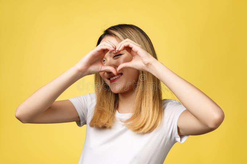 Giovane segno asiatico della mano del cuore di manifestazione della donna su fondo giallo immagini stock