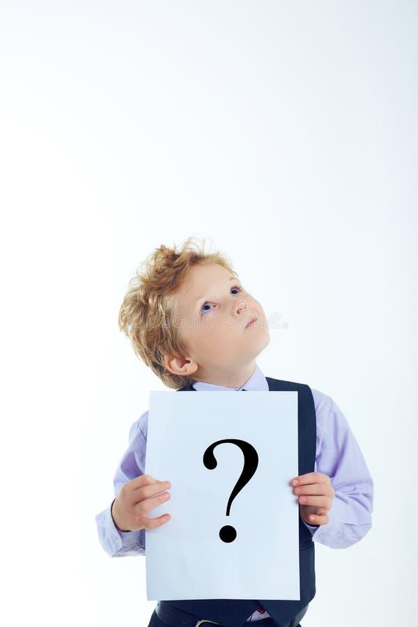 Giovane segno riccio del punto interrogativo della tenuta del ragazzo isolato su fondo bianco fotografie stock