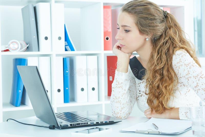 Giovane segretario con capelli ricci lunghi che si siedono davanti al suo computer portatile, esaminante schermo fotografie stock