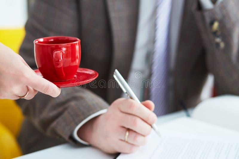 Giovane segretario porta il caffè al capo maschio Personale di servizio Concetto di tempo del caffè e tempo per una rottura fotografia stock