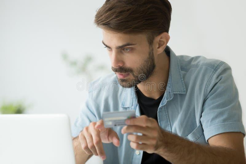 Giovane serio che compra online con la carta di credito ed il computer portatile fotografia stock libera da diritti