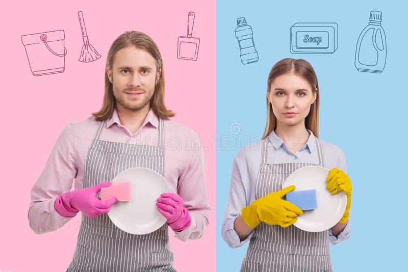Giovane serio che sta con la sua moglie calma e che lava i piatti immagini stock libere da diritti
