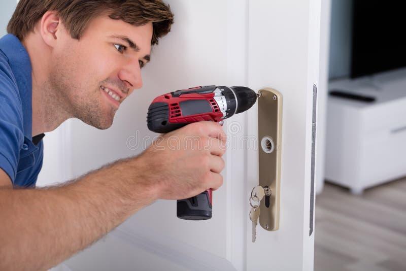 Giovane serratura di porta d'installazione maschio felice fotografia stock libera da diritti