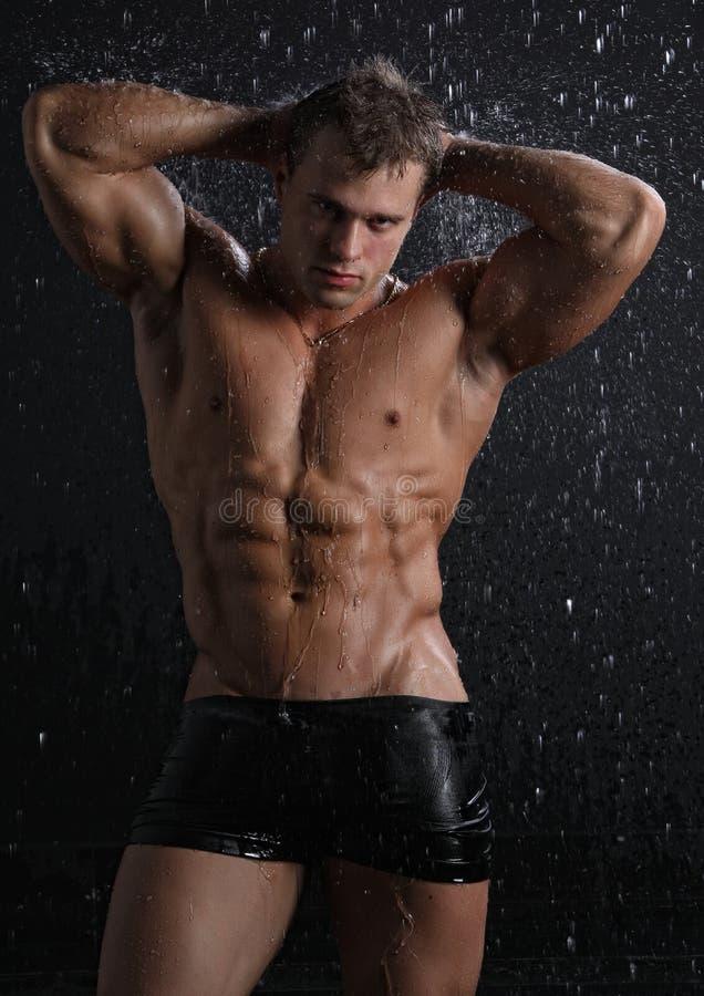 Giovane sexy del muscolo bagnato che propone sotto la pioggia