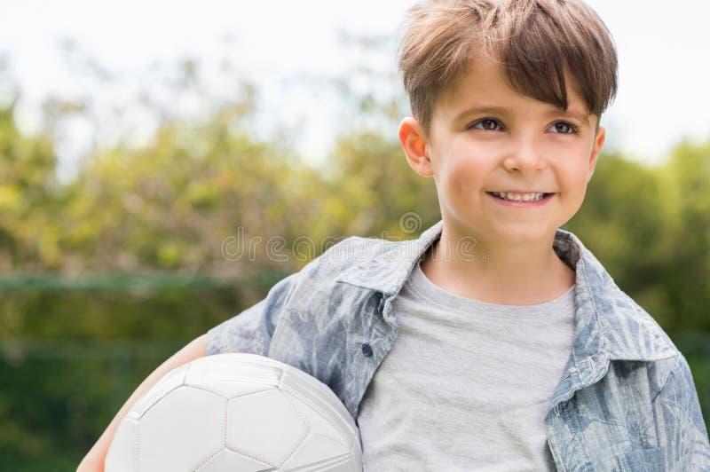 Giovane sfera di calcio della holding del ragazzo fotografie stock libere da diritti