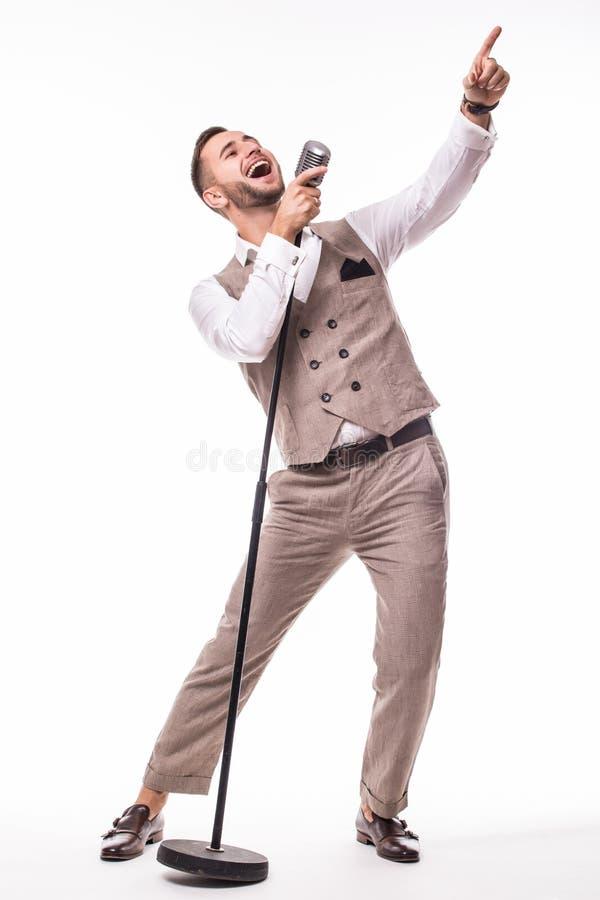 Giovane showman in canto del vestito con le emozioni e nel gesto aguzzo sopra il microfono con energia fotografia stock