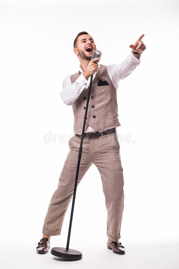 Giovane showman in canto del vestito con le emozioni e nel gesto aguzzo sopra il microfono con energia fotografie stock libere da diritti
