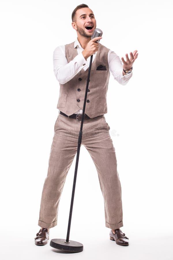 Giovane showman in canto del vestito con le emozioni e nel gesto aguzzo sopra il microfono con energia fotografia stock libera da diritti