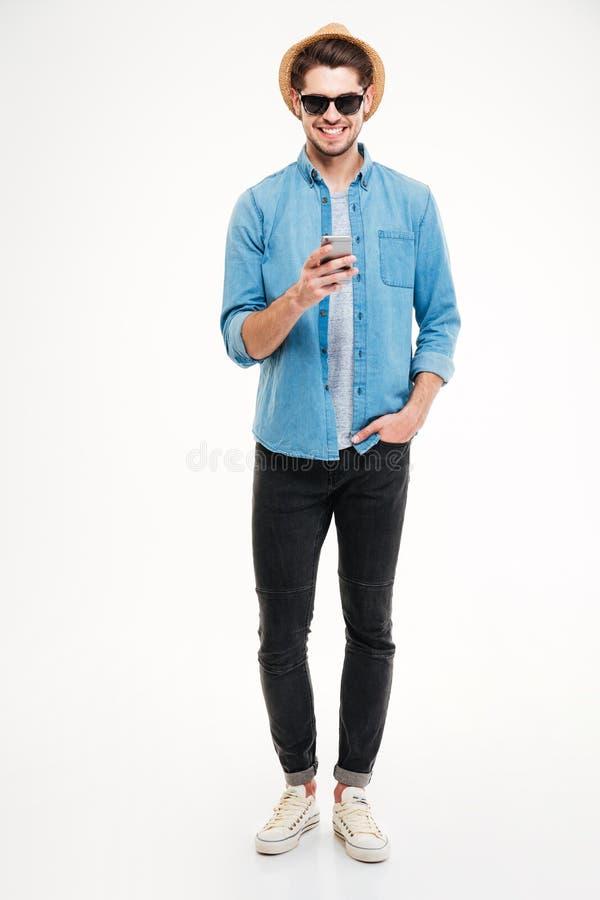 Giovane sicuro allegro in cappello ed occhiali da sole facendo uso dello smartphone fotografie stock libere da diritti