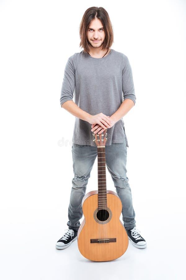 Giovane sicuro felice che sta con la chitarra fotografia stock libera da diritti